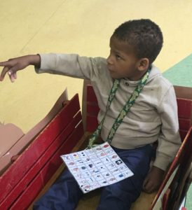 A student sitting in a wagon. A universal core board is attached to a lanyard around his neck.