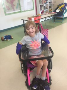 A smiling student in a wheelchair.