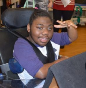 A student sitting in a wheel chair facing the camera.